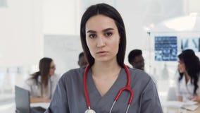 有听诊器的白种人女性医生在看对照相机和横渡的手一会儿的医疗衣裳的脖子 股票录像
