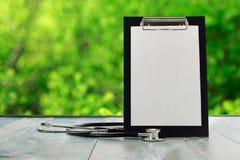 有听诊器的黑剪贴板在一张蓝色木桌上 库存照片