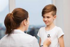 有听诊器的医生听愉快的孩子的 库存图片