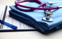 有听诊器的医生外套在书桌上 免版税库存图片
