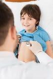 有听诊器的医生审查的微笑的小男孩 免版税库存照片