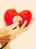 有听诊器的医生审查红色心脏的 图库摄影