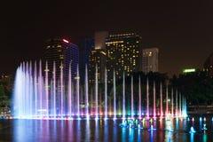 有启发性喷泉在晚上在现代城市 免版税库存图片
