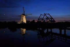 有启发性风车和一座吊桥在日落 库存图片