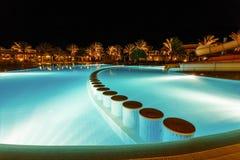 有启发性水池在与热带棕榈的晚上 免版税库存照片