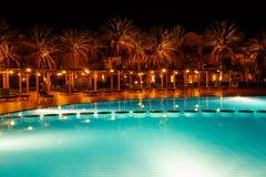 有启发性水池在与热带棕榈的晚上 库存照片