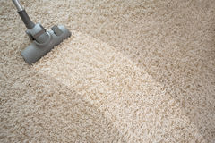 有吸尘器的吸尘的粗砺的地毯 图库摄影