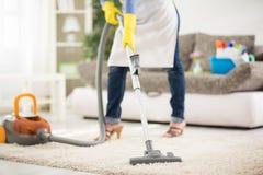 有吸尘器的妇女干净的地毯 库存照片
