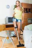 有吸尘器的白肤金发的妇女 免版税库存照片