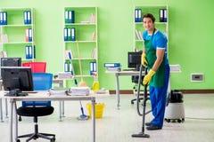 有吸尘器的英俊的人清洁办公室 免版税库存图片