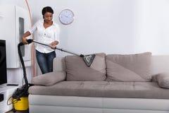有吸尘器的非洲妇女清洁沙发 库存照片