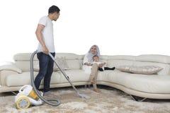有吸尘器的年轻丈夫清洁席子 库存图片
