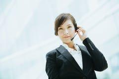 有吸引力亚洲女实业家佩带有话筒的耳机 免版税库存图片