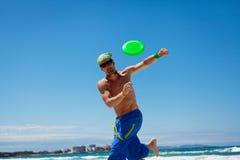 有吸引力人使用frisby在海滩在夏天 库存照片