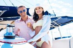 有吸引力和富有的夫妇有在小船的一个党 库存照片