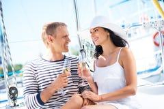 有吸引力和富有的夫妇有在小船的一个党 免版税库存图片