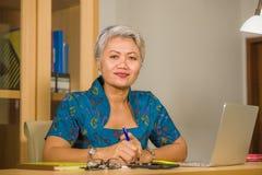 有吸引力和愉快的成功的中部变老了工作在手提电脑书桌微笑的确信的佩带的庄重装束的亚裔妇女  免版税库存图片