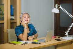 有吸引力和愉快的成功的中部变老了工作在手提电脑书桌微笑的确信的佩带的庄重装束的亚裔妇女  图库摄影