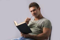 有吸引力和运动年轻人阅读书,看照相机 免版税库存图片