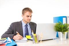 年轻有吸引力商人工作繁忙与便携式计算机在办公桌微笑的看满意 库存照片