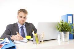 年轻有吸引力商人工作繁忙与便携式计算机在办公桌微笑的看满意 免版税库存照片