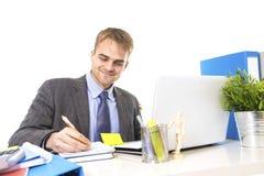 年轻有吸引力商人工作繁忙与便携式计算机在办公桌微笑的看满意 库存图片