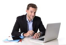 年轻有吸引力商人放松的工作愉快在满意的计算机书桌和微笑 免版税库存图片