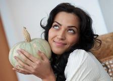 有吸引力女孩藏品南瓜微笑 免版税图库摄影