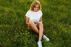 有吸引力女孩跨leged与她的手机坐g 库存图片