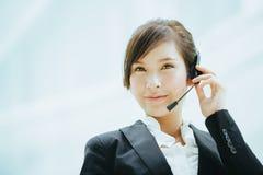 有吸引力女性亚洲女实业家佩带有话筒的耳机 免版税图库摄影