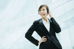 有吸引力女性亚洲女实业家佩带有话筒的耳机 库存照片