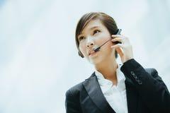 有吸引力女性亚洲女实业家佩带有话筒的耳机 免版税库存图片