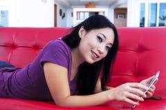 有吸引力女性在家说谎在红色沙发 免版税图库摄影