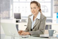 有吸引力女性研究膝上型计算机在办公室 库存照片