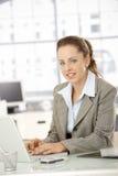有吸引力女性研究膝上型计算机在办公室 免版税库存图片
