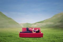 有吸引力女性说谎在室外红色的沙发 图库摄影