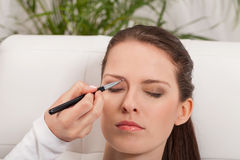 年轻有吸引力妇女构成眼眉粉末阴影申请 库存照片