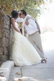 年轻有吸引力最近婚姻倾斜反对岩石墙壁亲吻的夫妇 库存照片