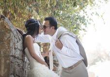 年轻有吸引力最近婚姻倾斜反对岩石墙壁亲吻的夫妇 免版税图库摄影