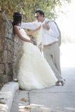 年轻有吸引力最近婚姻倾斜对岩石墙壁的夫妇 库存图片
