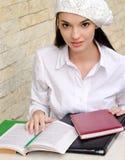 穿着贝雷帽的美丽的学生女孩。 免版税库存照片