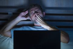 有吸引力疲乏和被注重的工作狂人工作夜间用尽在床上繁忙充满困手提电脑打呵欠的感觉 图库摄影