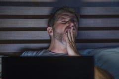 有吸引力疲乏和被注重的工作狂人工作夜间用尽在床上繁忙充满困手提电脑打呵欠的感觉 库存图片