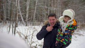 有吸引力的三口之家获得乐趣在雪冬天公园 使用外面在冬日的父亲和儿子 人投掷 股票视频