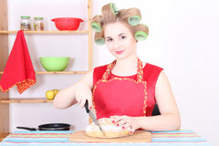 有吸引力的主妇剪切面包在厨房里 图库摄影