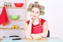 有吸引力的主妇剪切面包在厨房里 免版税库存照片