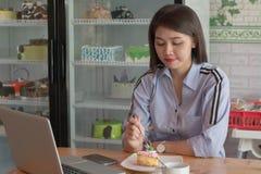 有吸引力的亚洲女性享用的切片在蛋糕商店的草莓蛋糕有膝上型计算机、智能手机和咖啡的 库存照片