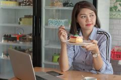 有吸引力的亚洲女性享用的切片在蛋糕商店的草莓蛋糕有膝上型计算机、智能手机和咖啡的 免版税库存图片