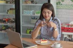 有吸引力的亚洲女性采取的图片切片与智能手机的草莓蛋糕对上载在社会媒介 库存照片