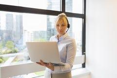 有吸引力的企业膝上型计算机妇女工作 耳机 楼b 图库摄影